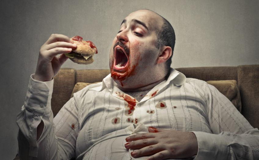 Voracious man eating a hamburger